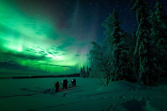 Фотографы снимают Северное сияние в Финляндии.
